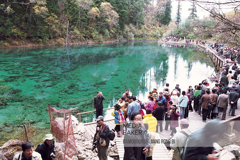 Tourists gathered beside a placid lake, The scenery of Jiuzhaigou scenic area , Nanping County, Aba State, Sichuan Province of People's Republic of China