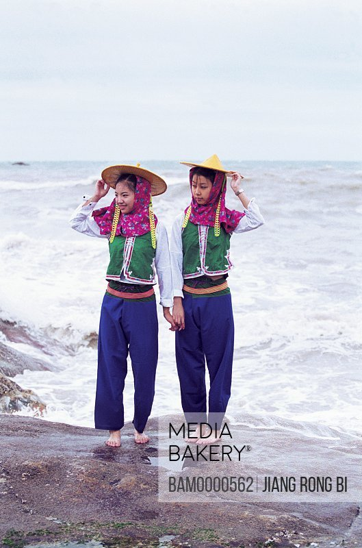 Girls standing on rocks by beach, Attractive Huian Ladies on Beach, Chongwu Town, Huian County, Fujian Province, People's Republic of China