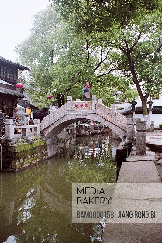 View of a woman standing on bridge, Yongan arch bridge of Jiaozhi region of rivers and lakes pond, Jiaozhi Town, Kunshan City, Jiangsu Province of People's Republic of China