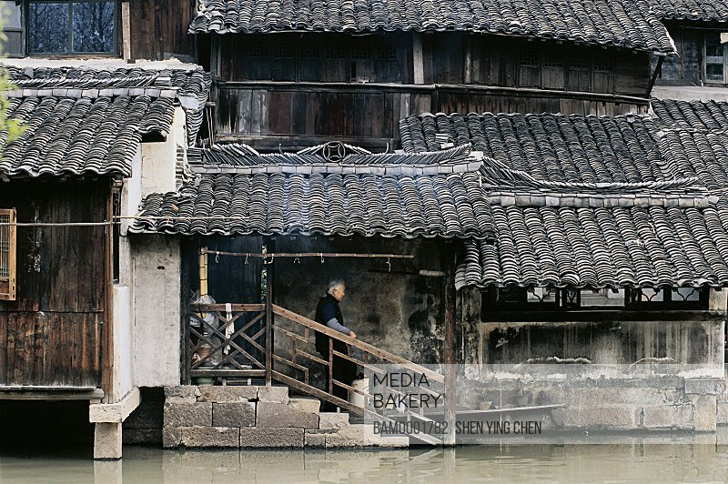 Person standing on stairs of house by lake, Millennium old town--Morning of the Wu Town, Tongxiang city of Zhejiang province in People's republic of China