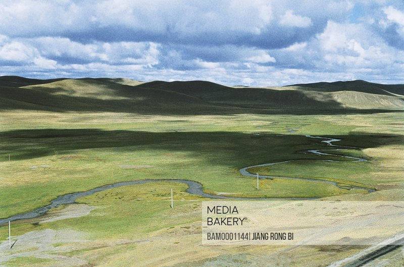 Elevated view of meandering stream passing through grassland, The scenery of Gonggeer Prairie, Keshiketengqi, Chifeng City Inner Mongolia Autonomous Region of People's Republic of China