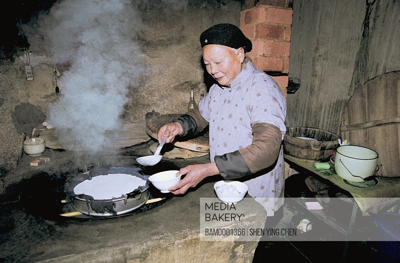 Senior woman cooking in the kitchen, The old man who Steams the lunar new year's cake at old Heping town in Shaowu, Heping town, Shaowu County, Fujian Province of People's Republic of China