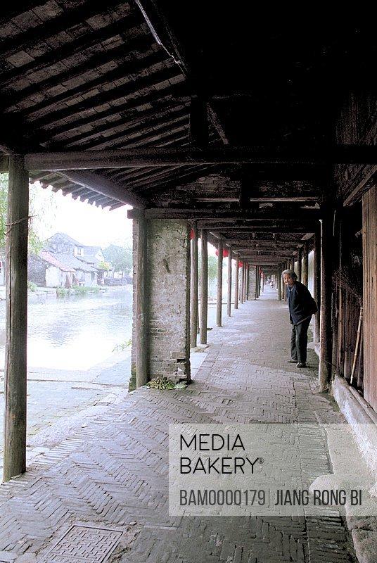 Senior woman standing in corridor, Ancient Corridor in Xitang Town, Jiaxing City, Zhejiang Province, People's Republic of China