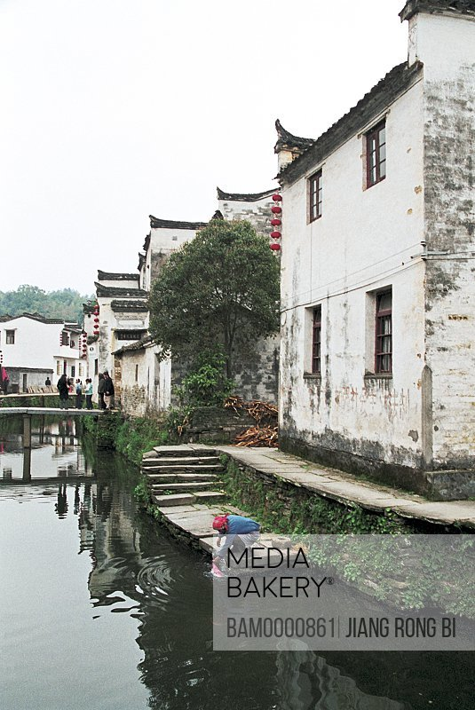 Person washing in stream by houses, Likeng Village by water and mountains, Likeng Village, Wuyuan County, Jiangxi Province of People's Republic of China