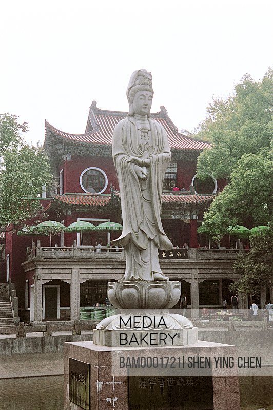 View of statue with temple in background, Goddess of Mercy pond of Yongquan Temple, Gushan, Fuzhou City, Fujian Province of People's Republic of China