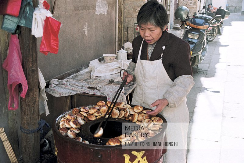 View of a woman preparing bread, Cake House in Old Street of Tunxi , Yixian County, Anhui Province, PRC