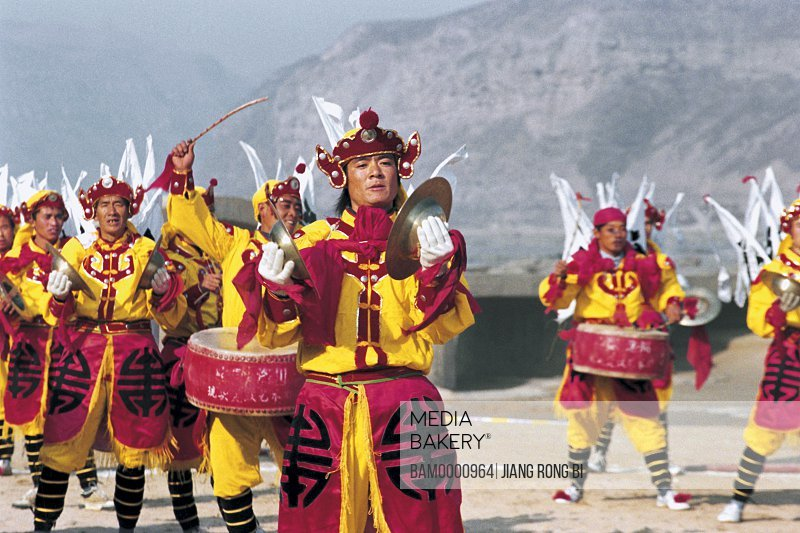 People in traditional clothing celebrating with drums, Luochuan Biegu Drum Show in Front of Huanghe River Hukou Waterfall, Yichuan County, Yan'an City, Shanxi Province, People's Republic of China
