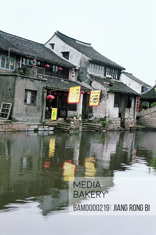 Reflection of houses and flags in canal, The historic building of Xitang region of rivers and lakes pond, Xitang Town, Jiashan County, Jiaxing City, Zhejiang Province of People's Republic of China
