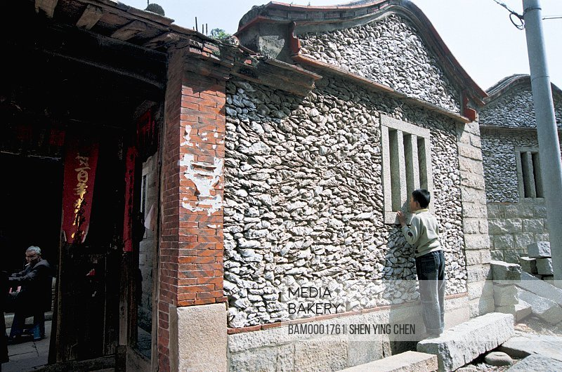 Boy peeping through window of shell house, Sea oyster shell house of Xunpu Village, Xunpu Village, Quanzhou City, Fujian Province of People's Republic of China