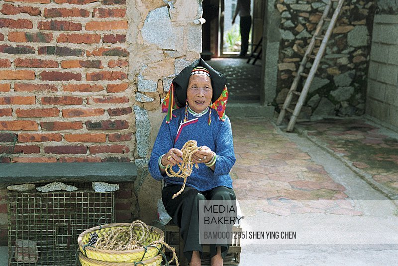 Senior woman sitting with ropes, Huian Women in Xiaozuo Village are rubbing the grass, Xiaozuo Village, Huian County, Fujian Province of People's Republic of China
