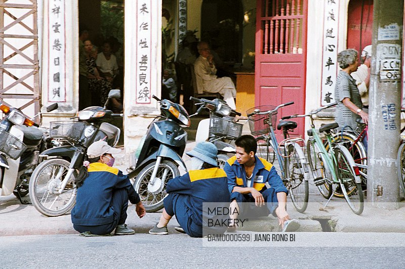 Cleaners sitting on street by parked vehicles, Hanoi City, Vietnam