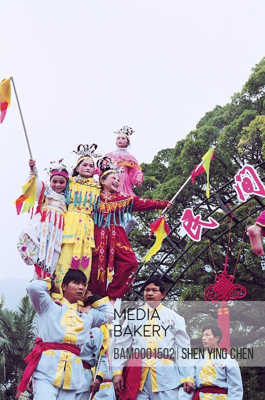 Low angle view of men carrying girls on shoulders during a festival, Winter jasmine folk art performance in country forest park---On the shoulder plays, Fuzhou City, Fujian Province of People's Republic of China