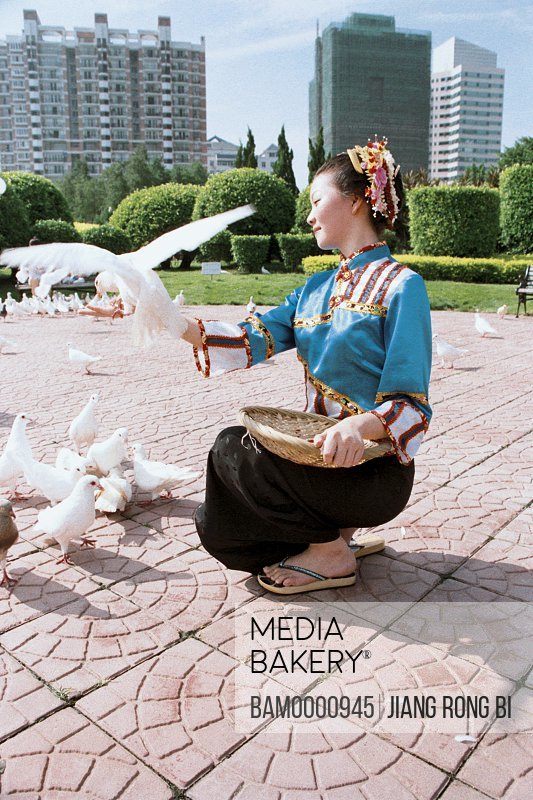 Side view of a cheerful girl playing with pigeon, Xunpu women at the photographic exhibition often Taiwan strait, Fuzhou City, Fujian Province, People's Republic of China