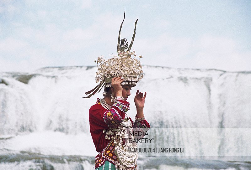 Performance of Miao minority girl under the Dupotong waterfull, Anshun City, Guizhou Province of People's Republic of China