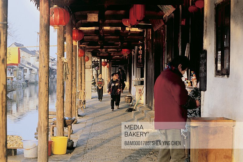 People in corridor of building by lake, Morning of the old Xitan Town, Jiaxing city of Zhejiang province in People'c republic of China