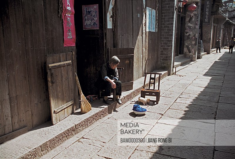 Senior woman sitting by a door, The house in the old street of Fenghuang ancient city, Fenghuang, Xiangxi Prefecture, Hunan Province, People's Republic of China