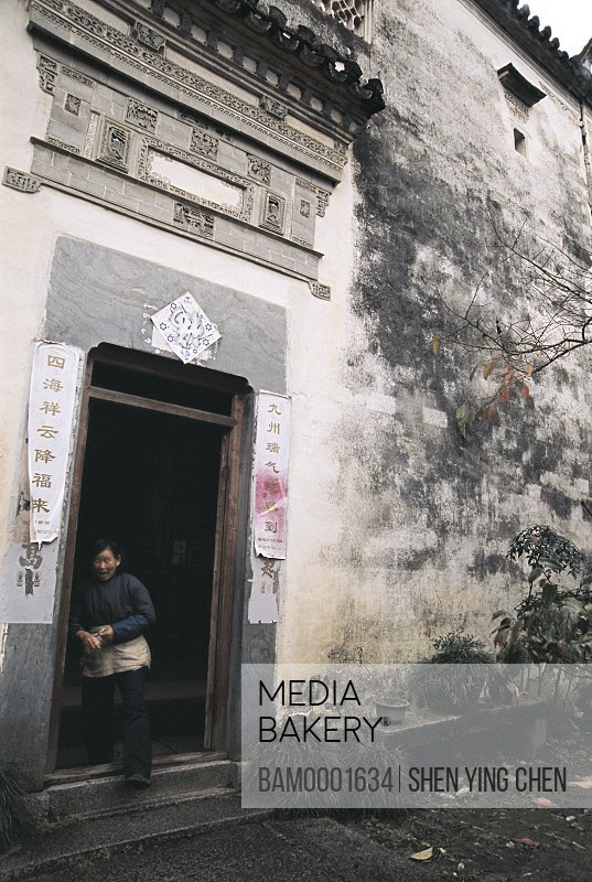 Mature woman standing at doorway, Lu Village's ancient common people residence of Ming and Qing dynasty, Lu Village, Yi County, Anhui Province of People's Republic of China