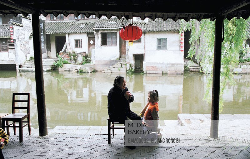 View of senior woman with granddaughter by canal, Grandma and granddaughter live in Xitang region of rivers and lakes pond, Xitang Town, Jiashan County, Jiaxing City, Zhejiang Province of People's Republic of China