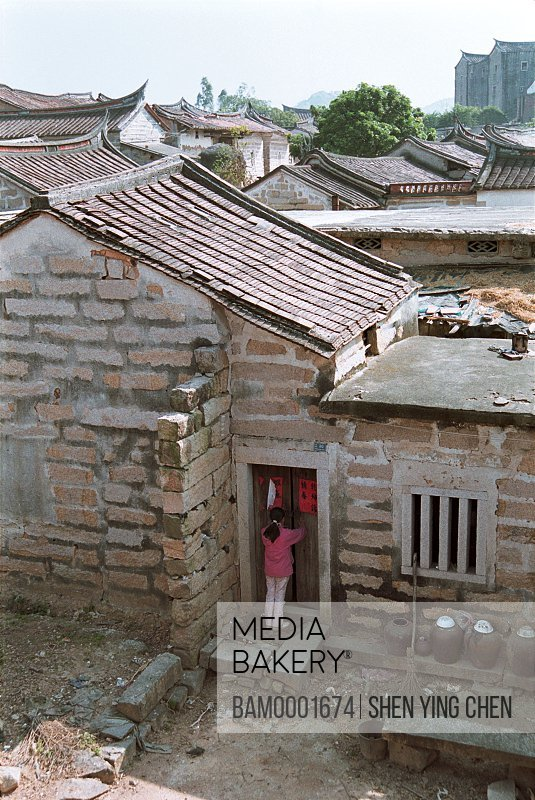 Elevated view of woman standing outside house, The ancient common people residence of Zhaojiabao, Zhaojiaobao, Zhangpu County, Fujian Province of People's Republic of China