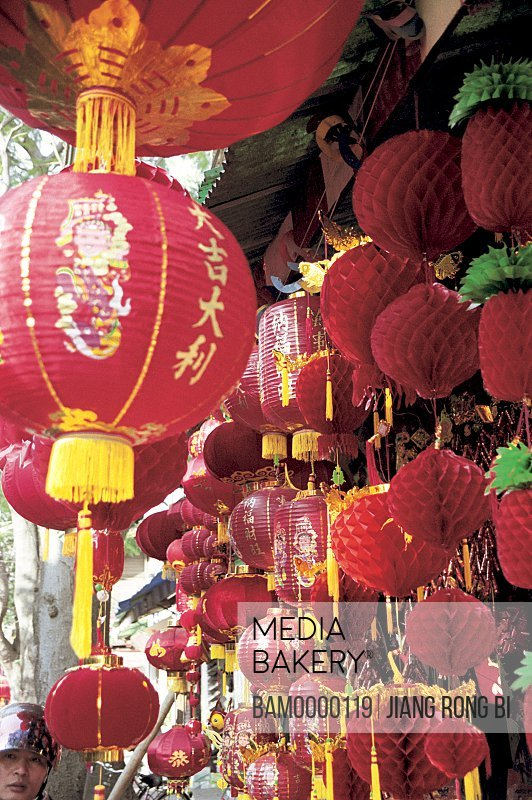 Mid adult man by Chinese lanterns in a shop, Nanhou street, Fuzhou City, Fujian Province, People's Republic of China