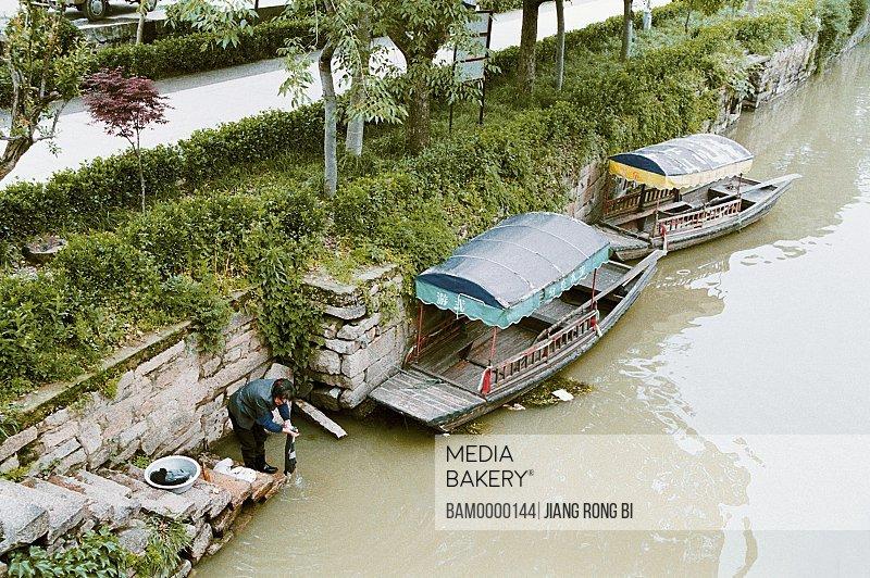 Woman washing clothes in river, Xiangxi river in old Mudu Town, Mudu Town, Suzhou City, Jiangsu Province of People's Republic of China