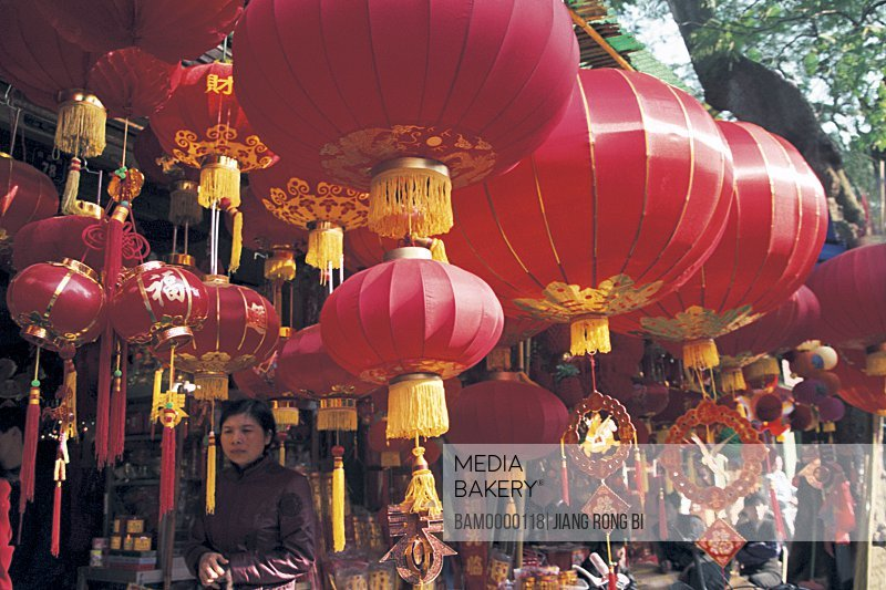 Mid adult woman standing under Chinese lanterns in a shop, Nanhou street, Fuzhou City, Fujian Province, People's Republic of China