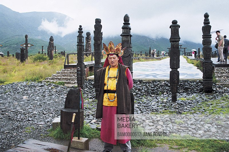 Man standing by carved pillars, Dongba Wizard in Dongba Park , Lijiang City, Yunnan Province, People's Republic of China