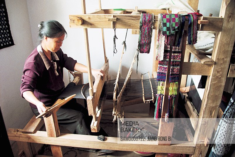 View of a woman working with handloom, Ancient weaving craft of the Shitouzhai village, Anshun City, Guizhou Province of People's Republic of China