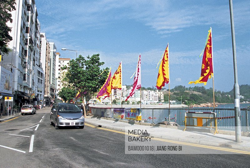 View of cars moving on the road with flags on railing, The street of Red Pillar, Hongkong special administration region of People's Republic of China
