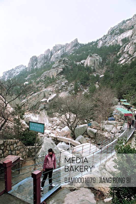 Elevated view of a woman standing on a bridge, The scenery of Lao Mountain, Qingdao City, Shandong Province of People's Republic of China