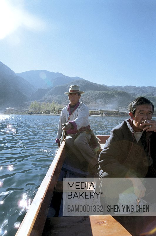 Portrait of men traveling in a boat, Shuttle clansman on the Lugu Lake, Lugu Lake, NingLang County, Lijiang City, Yunnan Province of People's Republic of China