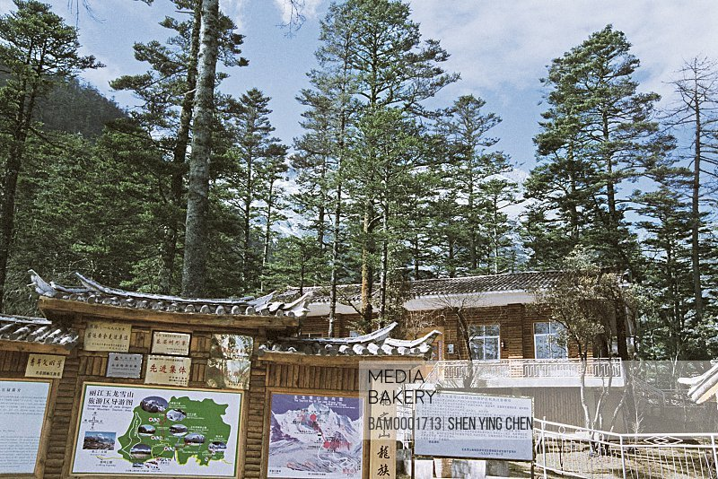 Maps displayed on notice board with trees in the background, Rope road junction of Yulong Snowy mountain, Yulong snowy mountain,Lijiang City, Yunnan Province of People's Republic of China