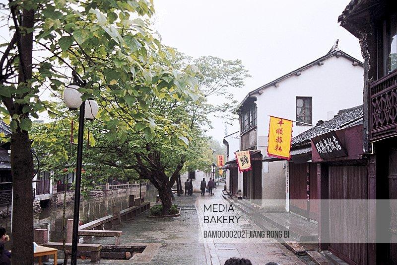 People walking on street beside houses, The double bridge restaurant in Zhouzhuang, Zhouzhuang Town, Kunshan City, Jiangsu Province of People's Republic of China