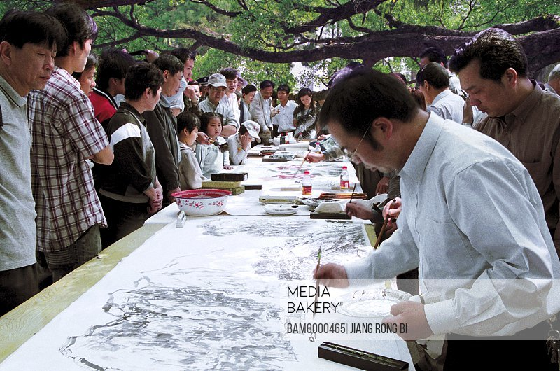 """People looking at paintings of artists, Painters Painting on-site for """"Banyan Festival"""" Held in Forest Park, Fuzhou City, Fujian Province, People's Republic of China"""