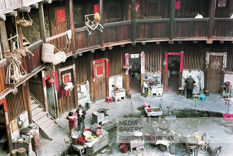 Elevated view of people standing at sidewalk of an old building, The family lives in viviparus pit earth building, Zhangpu County viviparus pit earth building, Fujian Province of People's Republic of China