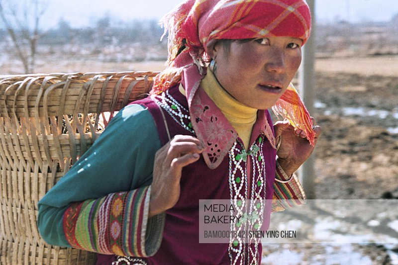 Portrait of a mid adult woman carrying a basket, Women of the Touches the shuttle race, Ninglang County, Lijiang City, Yunnan Province of People's Republic of China