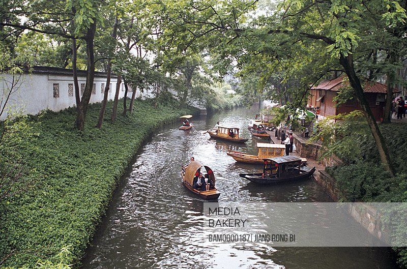 Elevated view of tourists traveling on boats in river, The yachts in old river of Suzhou, Suzhou City, Jiangsu Province of People's Republic of China