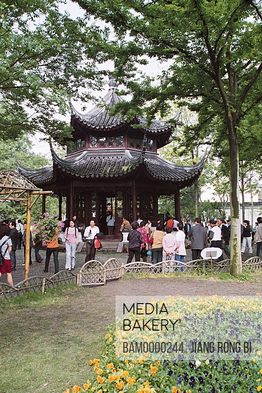 Tourists standing near pavilion in garden, Pavilion of Zhuozheng park, the symble of Suzhou park, Suzhou City, Jiangsu Province, People's Republic of China
