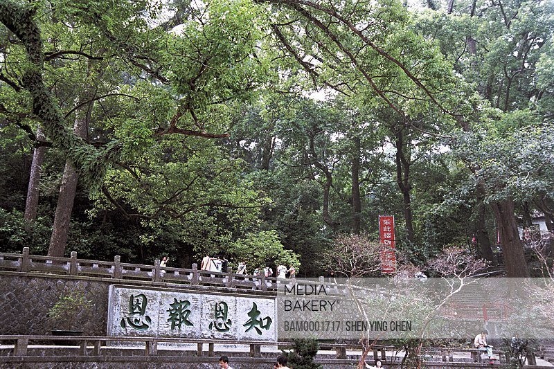 People standing by wall with Chinese text, Scenery of Yongquan temple, Gushan, Fuzhou City, Fujian Province of People's Republic of China