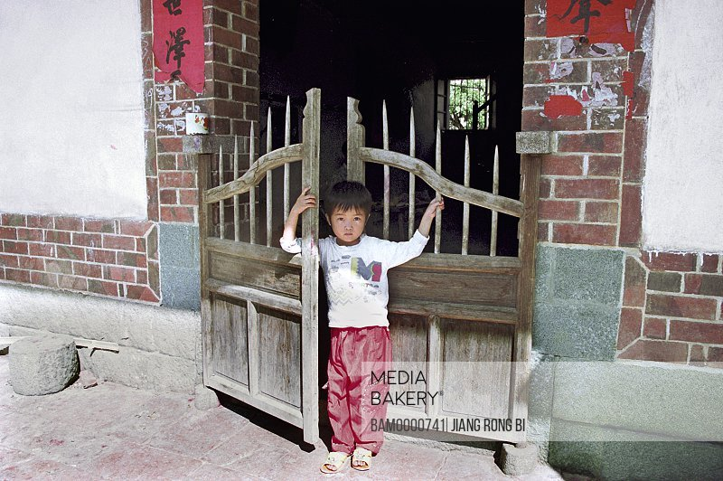 Portrait of a boy standing in front of the gate, Children from Yanshou Village, Chengxian District, Putian City, Fujian Province, People's Republic of China