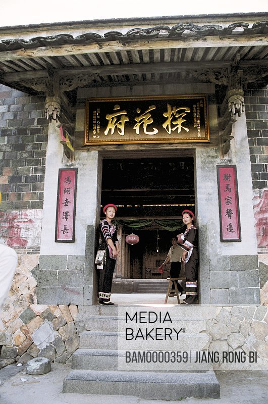Portrait of women standing at the door of a government building, The flowered government office of She minority village in Rixi township, Fuzhou City, Fujian Province, People's Republic of China