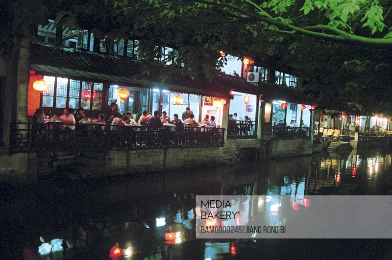 View of tourists sitting in restaurant by lake at night, The night scenery of restaurant of Zhouzhuang region of rivers and lakes pond, Zhouzhuang Town, Kunshan City, Jiangsu Province, People's Republic of China