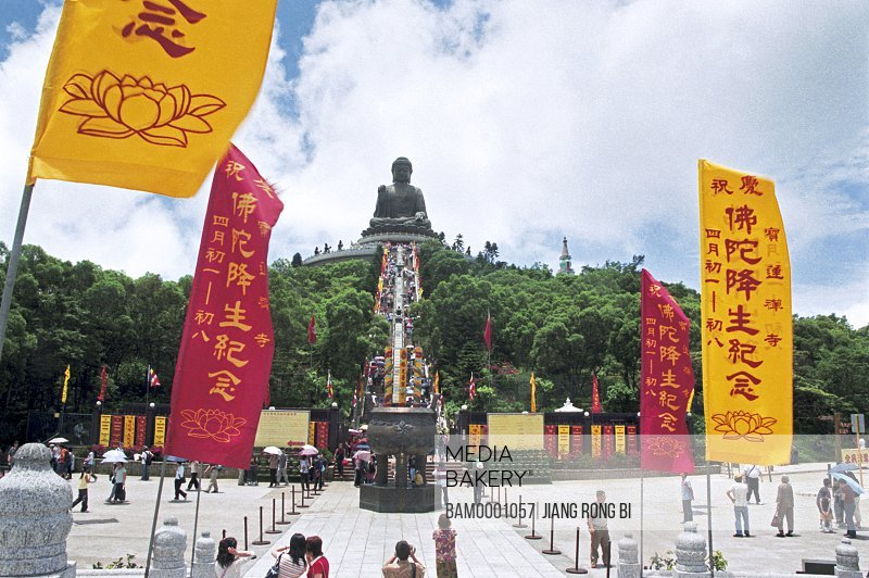 Low angle view of people gathered by statue with flags in foreground, The Tiantan buddhu in the Dayu Mountain, Hongkong special administration region of People's Republic of China