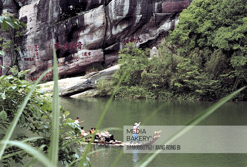 View of people traveling on bamboo raft with mountain in background, The Bamboo rafts of Jiuqu river in Wuyi mountain, Wuyishan City, Fujian Province, People's Republic of China