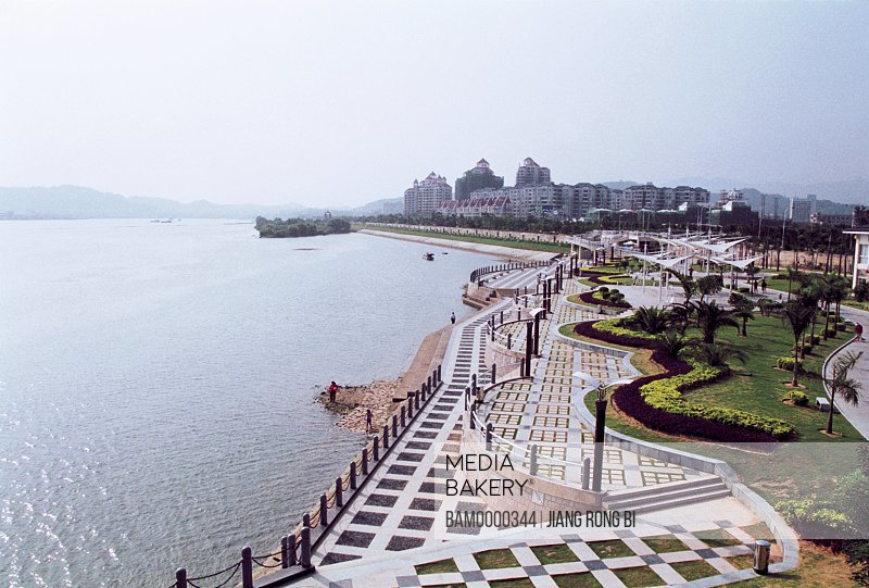 Elevated view of garden by river with buildings in background, Nanjiangbin park, Fuzhou City, Fujian Province, People's Republic of China