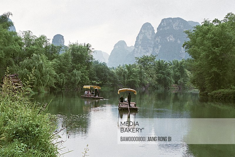 Tourists traveling on rafts with view of mountains in the background, The scenery of Minsi countryside in Detian, Daxin County, Nanning City, Guangxi Zhuang Nationality Autonomous Region of People's Republic of China