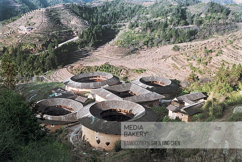 Elevated view of structures with mountains in background, Outdoor scene of viviparus pit, Zhangpu County viviparus pit earth building, Fujian Province of People's Republic of China