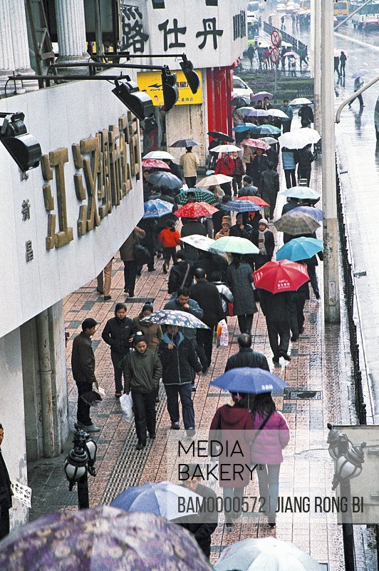 Elevated view of people walking on wet street, The rainy street of Jianghan Road, Wuhan City, Hubei Province, People's Republic of China