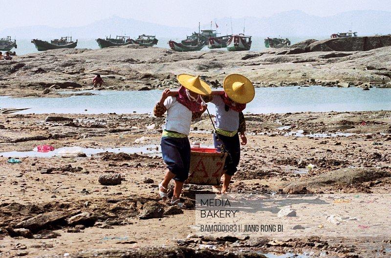 Huian women carrying basket with boats in the background, Chongwu Town, Huian County, Fujian Province, People's Republic of China