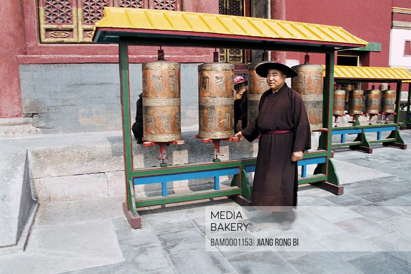 Mature man standing by prayer wheels in temple, The lama turnning typecasting sutra wheel, Chengde City, Hebei Province of People's Republic of China